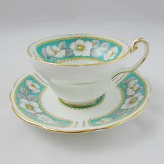 Foley tea cup in the Christmas Rose pattern. Tea cup and saucer are green with white roses. Gold trimming on cup and saucer edges. In excellent condition (see photos). Markings read: Foley Bone China Made in England Christmas Rose Please bear in mind that these are vintage items and
