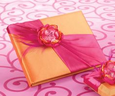 """This bold 8.5"""" x 6"""" guest book is covered in orange satin and accented on the front with a hot pink satin sash, hot pink feathers and a satin/tulle flower. The flower combines various shades of pink w"""