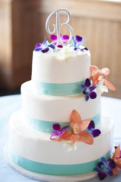 Three tiered white wedding cake with aqua ribbon trim and fresh tropical flowers.  Photo by Coleman Shots  www.engagingeventsobx.com  #engagingeventsobx #outerbankswedding