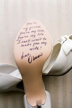 Groom writes the bride a message on the bottom of her wedding shoes. so sweet!