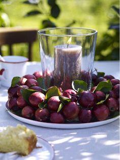 Kleine Zieräpfel auf einen Steckschaumkranz stecken, in die Mitte ein Glas mit passender Kerze.