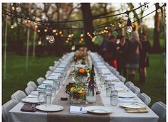 family-style table, white tablecloth with burlap runner, fall flowers, mason jars, bulb lights.