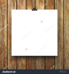 Close-up of one hanged square paper sheet frame with clip on brown vertical wooden boards background