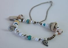 item #B063 The little mermaid bracelet is made with a beautiful assortment of sea shells, antique beads and trinkets, african heishi beads, a beautiful silver clam shell, silver lotus flower charm that all little mermaids treasure.
