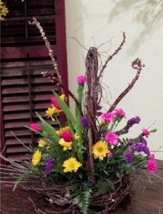 Springtime arrangement in a whimsical twig basket includes pussy willow, tulips and and other bright seasonal flowers.