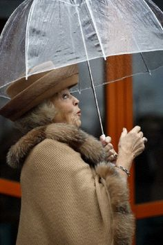 Dutch Queen Beatrix protects herself with an umbrella from the rain as she attends the opening of 'Cultuur Kwartier Sneek'