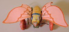 "1930's Tin Litho with Celluloid Wings Key Wind Butterfly! Unique find in a 1930's toy. Lithoed tin body with pink celluloid wings.  Wind up key on the side. 5"" across the wings. 2-1/2"" length of the body [click for details]"