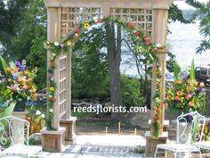 Pretty on-site arch at this ceremony was decorated to compliment and highlight the bride and groom. Flowers by www.reedsflorists.com Highlight, Compliments, Floral Design, Arch, Wedding Decorations, Groom, Reception, Outdoor Structures, Rustic