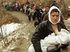 An ethnic Albanian woman feeds her baby as she and another 2,000 refugees, displaced by the war in Kosovo, are allowed to enter Macedonia in the mountainous region near the border crossing of Blace in March of 1999. More than 2,000 Kosovo refugees entered Macedonia after crossing the mountains in south Kosovo overnight. The refugees were blocked by the Macedonian army for several hours and spent the night in the forest, but were later allowed to enter Macedonia after UNHCR officials put…