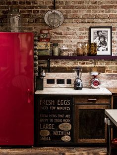 an industrial kitchen with brick wall, open shelves and a shiny red fridge to make a statement with color
