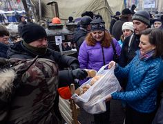 US Assistant secretary of State for European and Eurasian Affairs Victoria Nuland (R) distributing cakes to protesters on the Independence Square in Kiev on December 10, 2013. (AFP Photo / Party Press-Service / Andrew Kravchenko)