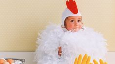 This baby chicken costume is made from two tickly feather boas, ordinary kitchen gloves, yellow tights, and a pilot's cap that's crowned with a felt comb.
