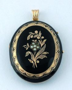 Victorian 9ct gold and black enamel, oval mourning locket with applied gold and seed pearl decorations, a double glazed locket interior, a photograph, hair and a reeded bale