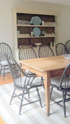 Dining room featuring striped woven rug of recycled plastics, David Lee furniture hutch, painted windsor chairs