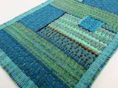 """This work is the 11th in a series of """"Remnants"""", which were all inspired by very old, heavily patched and stitched textiles.  I used Kaffe Fassett shot cottons and ikat fabrics, (which were created in conjunction with Oxfam, an international charity that champions fair trade, thus helping to support the poverty-stricken weaving villages in India and Guatemala where the cloth is produced).  The threads are Sulky 12wt blendables."""