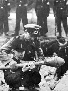 Preparing for the defense of Berlin. A German noncommissioned officer teaches a member of the Hitler Youth the skills of firing a Panzerfaust, grenade launcher. World War Two 1945