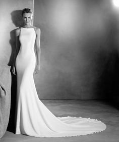 EMMETT is a mermaid wedding dress designed with crepe. A beautiful dress with an asymmetric neckline and gemstone details.