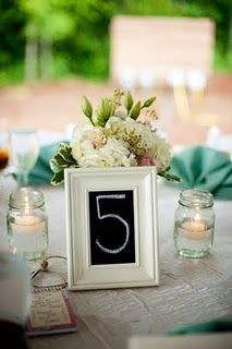 Pretty centerpiece with chalkboard table Numbers - use chalkboard markers rather than chalk, and find someone with excellent handwriting.