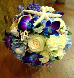 With you, life's a beach! Beach themed bridal bouquet with white dolomiti roses, electric blue dendrobium orchids, delphinium, blue hydrangea, dusty miller, fuschia waxflower and white spray roses with accents of starfish and assorted sea shells.