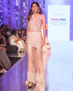 The Oyster Shell Gown The Oyster Shell gown exuberates the spirit of modern fashion. The gown is a melange of rich embroideries in summer sequins along with traditional sadi and kasab beautification. The timeless couture is comprises of a embellished halter neck, a sexy body gown silhouette followed by a heavily hand-done back trail. The cocktail creation is classic yet versatile with an avante-garde modern touch to it. Halter Neck, Sexy Body, Modern Fashion, Reflection, Trail, Shell, Cocktail, Sequins, Spirit