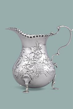 This sterling silver creamer is a wonderful example of Victorian-era  silversmithing. Surrounded by a rocaille motif of intricate repoussé and chased floral bouquets, this vessel is punctuated by delicate pad feet, a graceful scroll handle and scalloped rim–elements that give this piece an air of elegance and refinement. Hallmarked London, 1850 ~ 19th Century England, Silver Serving Pieces ~ M.S. Rau Antiques