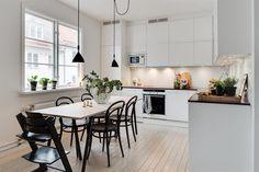 Stilrent kök som går i ljusa toner och bjuder på moderna materialval. Skåpsinredning med vita skåpsluckor från Ballingslöv och bänkskivor i stenkomposit.