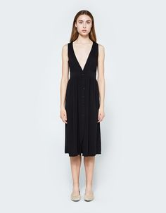 Easy dress from Farrow in Black. Deep V-neckline. Thick straps. Concealed front button closure. Defined waist with gathered detail. Full skirt. Straight hem. Unlined. Below-the-knee length. Casual fit.  • Lawn • 100% rayon • Hand wash, hang dry