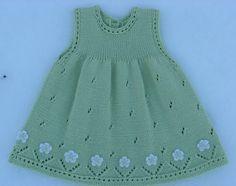 Vestido para niña, tejido con dos agujas, calado,  con aplicaciones de flores tejidas a crochet, en el ruedo.