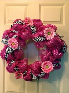 Hot pink deluxe deco mesh with zebra ribbon entwined and pink daisies scattered around the wreath.