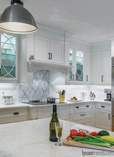 An elegant mosaic #tile focal point behind the range breaks up the subway tile used for the #backsplash throughout the rest of this #white #kitchen. #housetrends