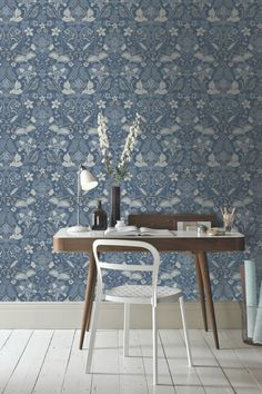 A beautiful Arthouse wallpaper design featuring a trailing damask pattern of flowers and birds in denim.