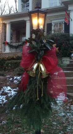 Christmas 2013 - Gold Bells, Gold Cording, Bright Red Deco Mesh Bow, Magnolia, and Greenery adorn this Lamp Post to welcome family and friends!