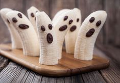 Homemade halloween scary banana ghosts monsters with chocolate faces. Healthy natural vegetarian snack recipe for party decoration on vintage wooden table background. Halloween Fingerfood, Dulces Halloween, Halloween Fruit, Healthy Halloween Treats, Homemade Halloween, Halloween Kids, Haloween Snacks, Halloween Saludable, Halloween Recipe