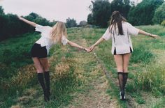 chicas tomadas de la mano caminando sobre las vías del tren