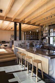 U-shaped semi-industrial kitchen with stainless steel cabinets and benchtops