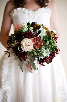 A rustic wedding bouquet features pincushion blooms, succulents and dusty miller to name a few.