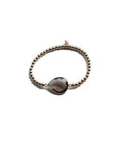 Sieraden PS call me smokey bracele - Goudkleurige armband met ronde balletjes en een ovalen taupekleurige natuursteen. De armband heeft een doorsnede van 5.5 cm, is elastisch, gemaakt van sterling zilver 925 met gouden plating en verkleurt niet.