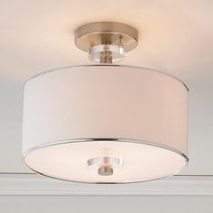 """Modern Sleek Semi-Flush Ceiling Light The white faux suede drum shade is accented with satin nickel and flanked top and bottom with acrylic discs to create this modern semi-flush ceiling light. The bottom diffuser completes the sleek look of this ceiling light and cuts down on glare. 3x60 watts medium base sockets. (11.5""""Hx13""""W)"""