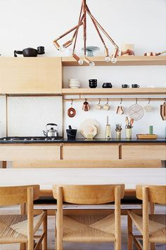 Warm wood goes great with copper, as evidenced in this minimalist Scandinavian kitchen. The wood cabinets and dining chairs are complemented by warm copper tones and black accents.