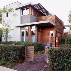 Stained wood siding adds warmth to this modern facade. More exterior color schemes: http://www.bhg.com/home-improvement/exteriors/curb-appeal/best-exterior-house-color-schemes/?socsrc=bhgpin040813woodsiding=6
