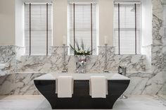 Gray Bathroom with Freestanding Black Tub containing: Granite Wall with Metal Candle Stick also Horizontal Window Blind plus Metal Flower Vase together with Pedestal Bathroom Set