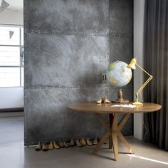 Metal room divider  This quietly sculptural pedestal table contrasts brilliantly with the harsh metal room divider behind, adding warmth and soul to the look.