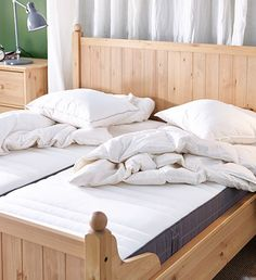 IKEA double bed and two single-sized bare mattresses