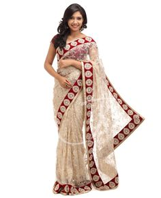 Off white net fancy saree.   Body :Off white color net with complete golden n off white color thread work with border.  Border :Attached maroon velvet fancy border worked with stones n pearls  Pallu :Off white color net with complete golden n off white color thread work with border  Blouse :	Maroon color velvet blouse with saree border