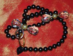 Bracciale perle nere, fiocchi in cristallo color oro, perla centrale oro satinato, la chiusura riporta le medesime cromie enfatizzando i cristalli stessi. Perla finale coperta di morbido tulle nero. Intrecci lucidi...