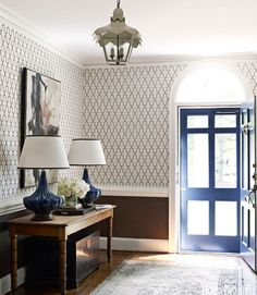 In the entry of a Charlotte, North Carolina, house, designed by Lindsey Coral Harper, walls in Phillip Jeffries's Moroccan on Manila Hemp grass cloth are grounded by the brown wainscoting.   - HouseBeautiful.com