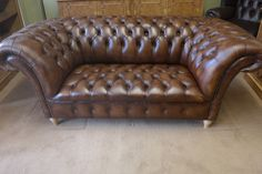 A two seat Victorian style leather chesterfield sofa. Buttoned upholstery. Wooden turned feet.