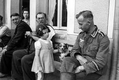 German Soldier with a little French girl. Interesante escena. Soldado alemán con aspecto de cansado (notese la distinción en el brazo). La mirada de la niña como extrañada y la de los otros civiles con actitud de disgusto ante el soldado del ejército invasor. ¡ Excelente foto!