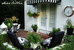 backyard patio - big clock + striped awning over French doors + lots of plants