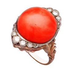 Russian Coral Diamond Ring 20th Century,  This distinctive Russian ring features a round coral cabochon measuring approximately 15 mm (1/2 in.) The ring is set on each side with three round diamonds in silver and mounted on a foliate-capped rose gold shank.  20th century, with Russian hallmarks. 1stdibs.com.